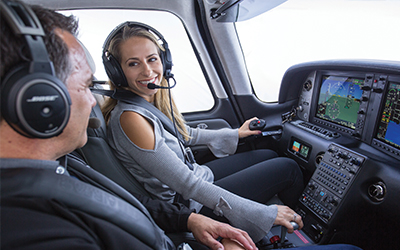 A man and a woman flying a cirrus aircraft